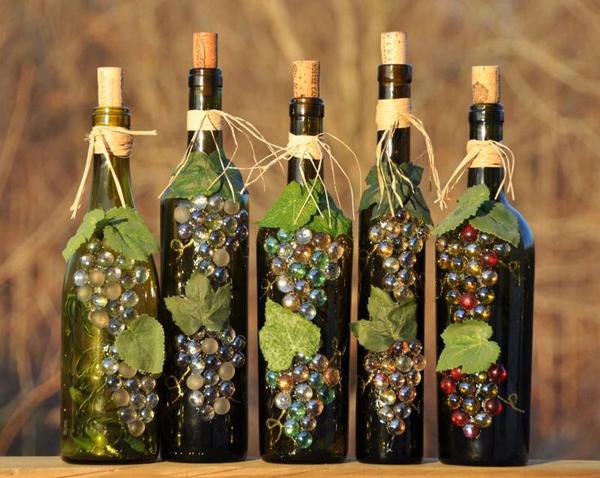garrafa de vidro com uvas e sisal