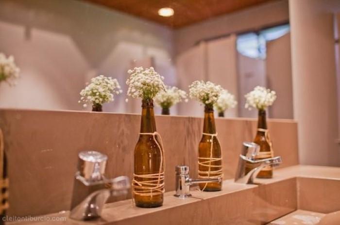 enfeite de mesa com garrafa, flores e sisal