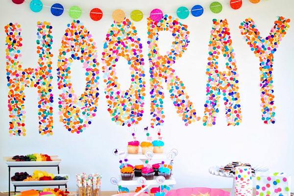 Enfeite de aniversário usando confetes na parede