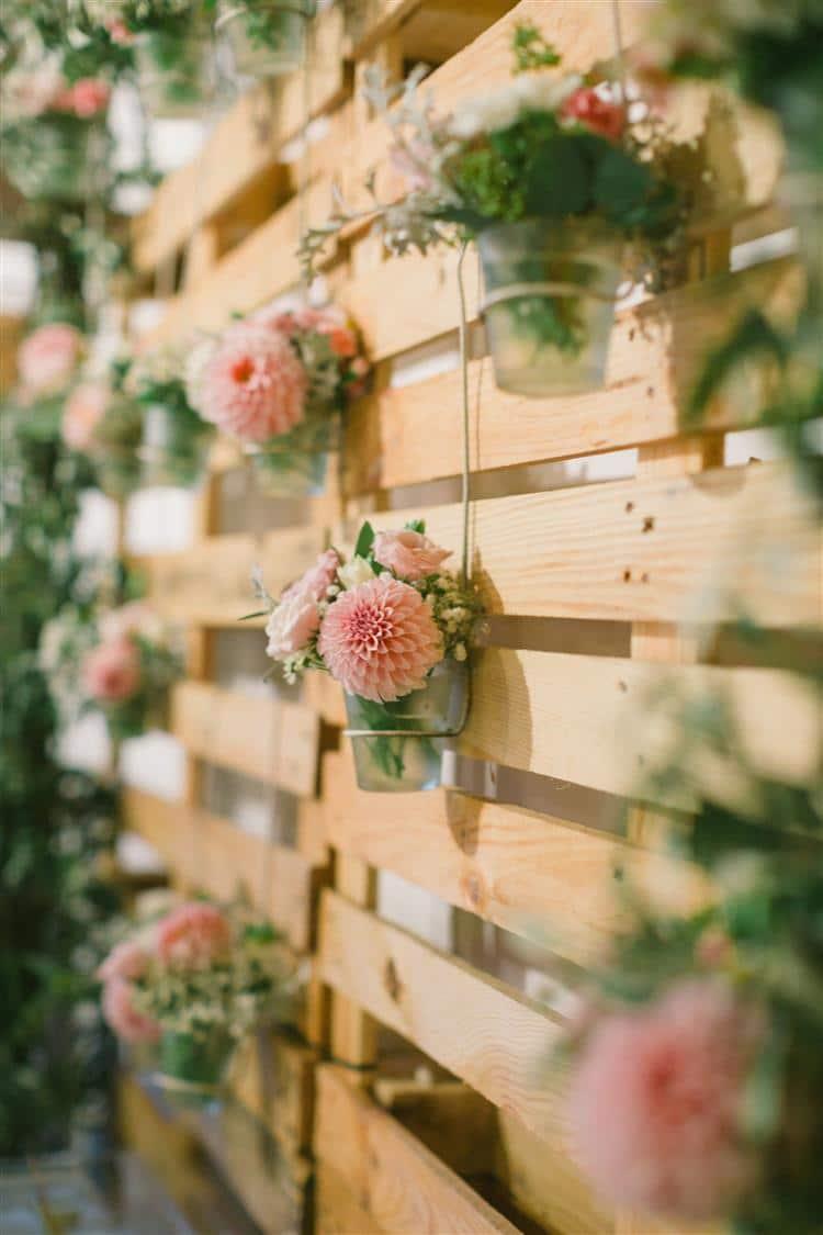 Palete de madeira com flores nos vasos