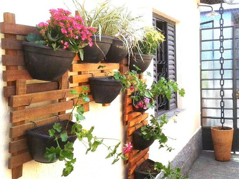 Jardim vertical de madeira e vasos de plástico