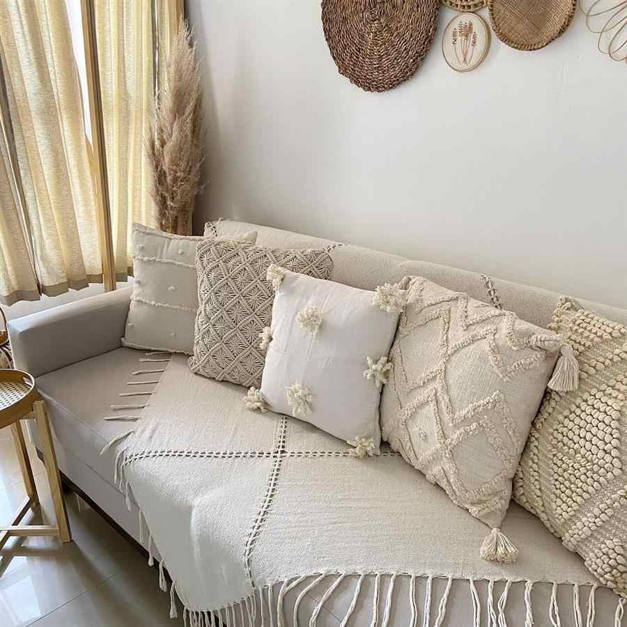 Sofá decorado com manta e almofadas